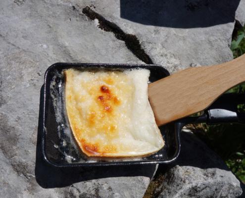 Présentation d'une raclette gratinée dans un poêlon du réchaud de plein air fouclette